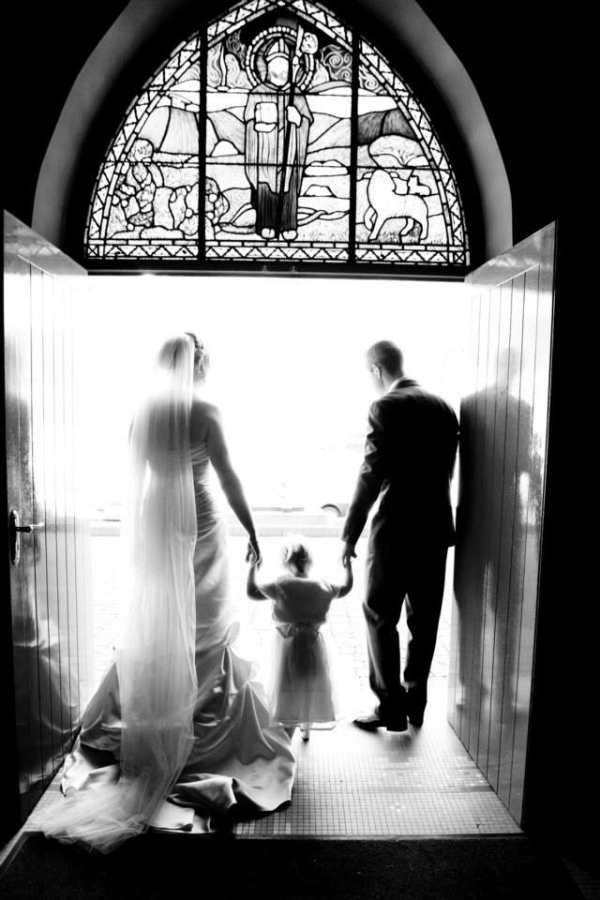 bride, groom and girl in church door